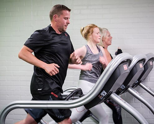 group of people in gym on running machine