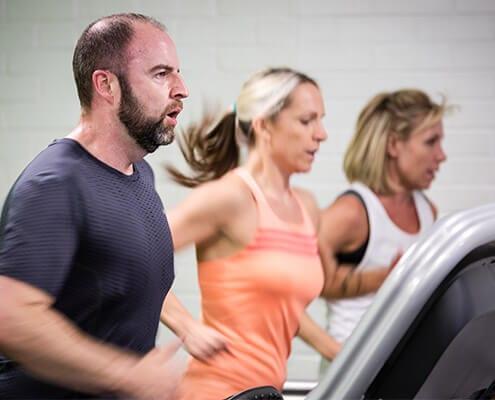 3 people running on treadmills in gym